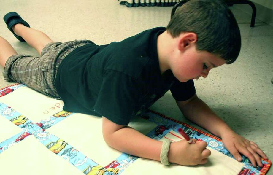 SPECTRUM/Brayden Ganser thoughtfully decorates a memory quilt, in memory of his dad, during Camp Jonathan. The Mountain Laurel Quilters annually supply two dozen handmade memory quilts to Camp Jonathan. August 2011  Courtesy of the New Milford VNA Photo: Deborah Rose