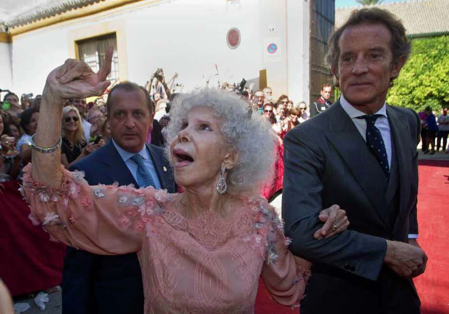 Maria del Rosario Cayetana Alfonsa Victoria Eugenia Francisca Fitz-James Stuart y de Silva, Spanish Duchess of Alba, reacts in presence of her husband Alfonso Diez after their wedding at Las Duenas Palace in Seville, Spain Wednesday Oct. 5, 2011. A wealthy, 85-year-old Spanish Duchess of Alba considered the world's most title-laden noble married a civil servant 25 years her junior, shrugging off her children's qualms and celebrating by kicking off her shoes and dancing a bit of flamenco.(AP Photo/Miguel Angel Morenatti) Photo: Miguel Angel Morenatti, Associated Press / AP