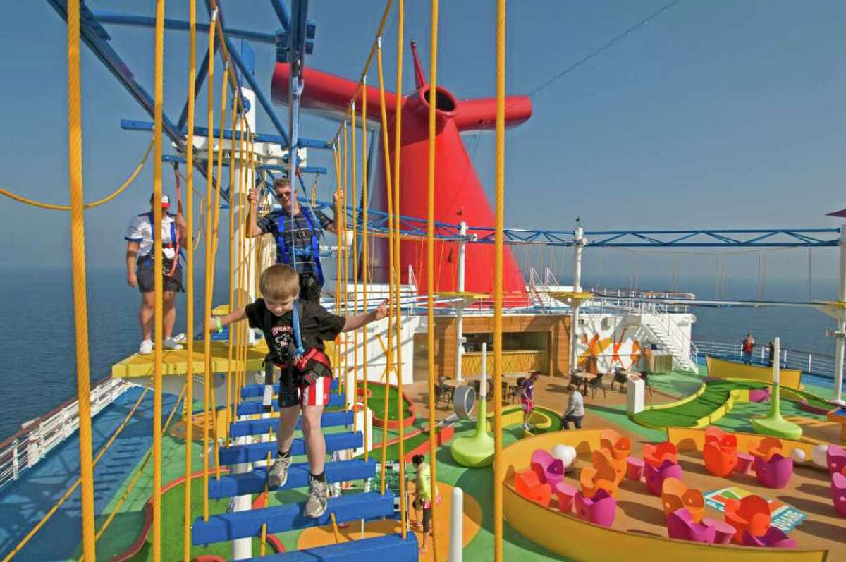 ANDY NEWMAN : CARNIVAL CRUISE LINES HIGH ABOVE THE SEA: Guests on board the Carnival Magic try out SkyCourse, the first-ever ropes course in which participants can traverse suspended cables with views 150 feet to the sea below.