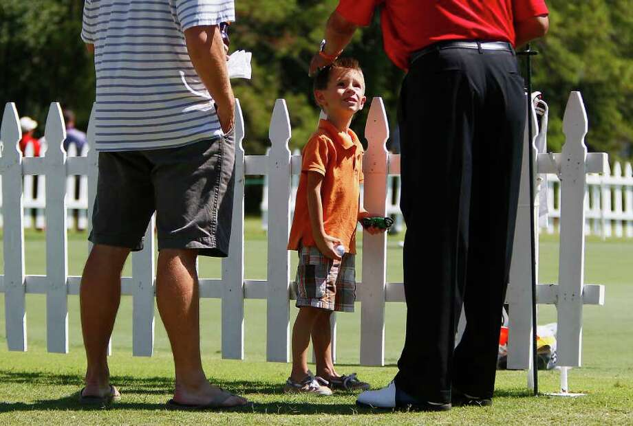 Brennen Young, 4, gets a pat on the head from pro golfer  Eduardo Romero, who gave him a signed ball during the Woodforest National Bank Championship Pro-Am at the Insperity Championship. Photo: Karen Warren, Houston Chronicle / © 2011 Houston Chronicle