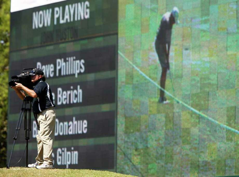 Photographer Danny Strickland, with Information and Display Systems,  shoots video for the big screen of golfers on the 18th hole. Photo: Karen Warren, Houston Chronicle / © 2011 Houston Chronicle