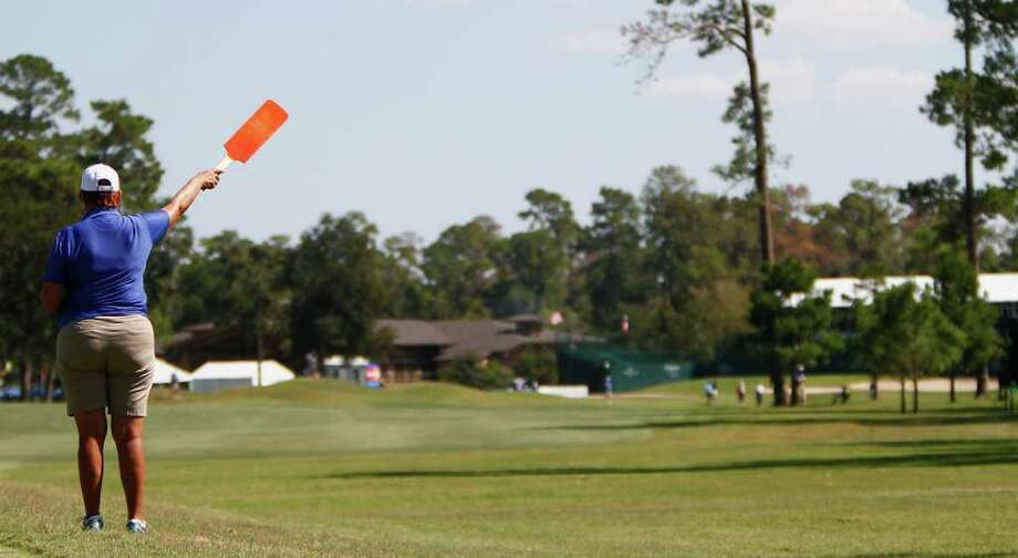 A hole marshal signals with her paddle on the 18th hole. Photo: Karen Warren, Houston Chronicle / © 2011 Houston Chronicle