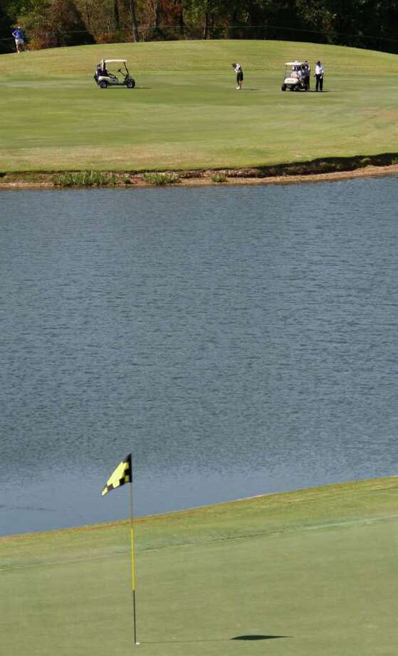 Golfers try to hit over the water on 17th hole during the Woodforest National Bank Championship Pro-Am at the Insperity Championship at The Woodlands Country Club. Photo: Karen Warren, Houston Chronicle / © 2011 Houston Chronicle