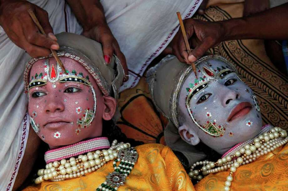 Indian artists Kandha Panday, right, and Shiva Sharma dressed as Hindu god Rama and his brother Lakshman have paint applied to their faces ahead of a religious procession during the Dussehra festival in Allahabad, India, Wednesday, Oct. 5, 2011. The Dussehra festival commemorates the victory of Rama over Ravana, an evil ruler who had abducted Rama's wife, Sita Devi. Rama killed Ravana to free Sita. The burning of effigies of Ravana, signifying the victory of good over evil, brings the festivities to a close. Photo: Rajesh Kumar Singh, Associated Press / AP