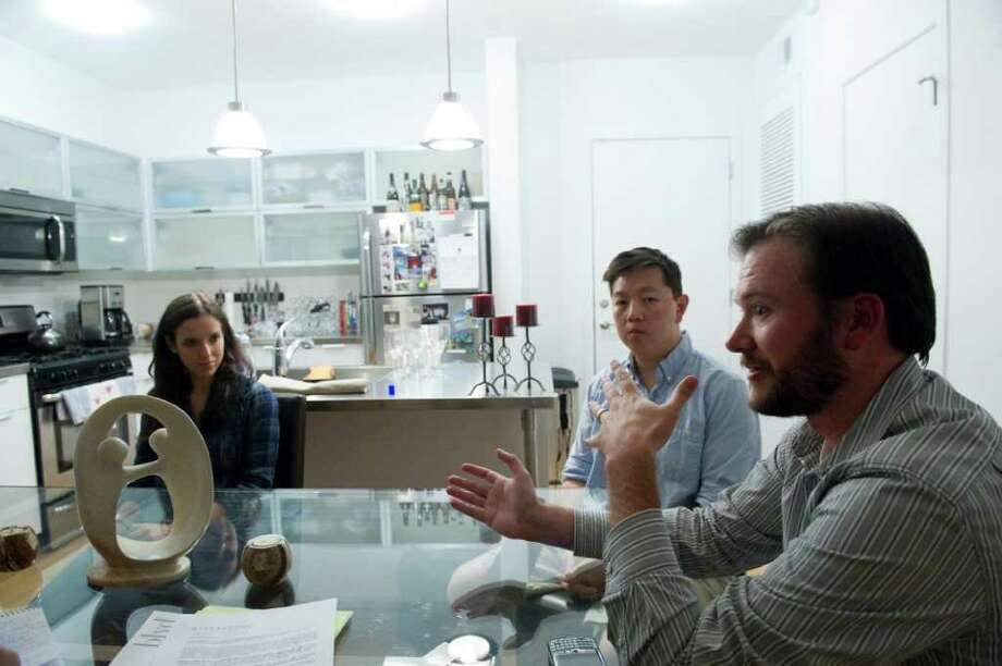 Mike Hume, right, his wife Kristin, left, and Ray Le discuss the realities of living at the BLVD as they sit around the Hume's kitchen table in Stamford, Conn., September 29, 2011. After one of the original developers of the much heralded Blvd apartment building downtown sold his share, residents are complaining that many of the amenities that drew them to the building are no longer available and security has decreased. Photo: Keelin Daly / Stamford Advocate