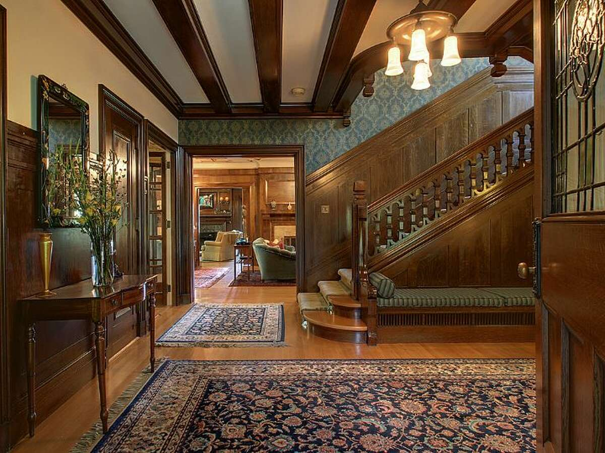 Foyer of 1039 Belmont Place E. The 8,243-square-foot brick tudor, built in 1913, has five bedrooms, 6.25 bathrooms, dark-stained wood moldings, beams and paneling, five fireplaces and distinctive windows and ceilings, and sits on a 14,400-square-foot lot with views of Lake Union, Puget Sound and the Olympic Mountains. It's listed for $3.8 million.