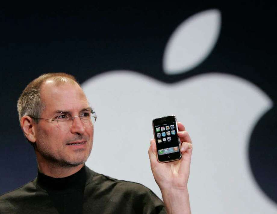 In this Jan. 9, 2007 file photo, Apple CEO Steve Jobs holds up an Apple iPhone at the MacWorld Conference in San Francisco. Photo: Paul Sakuma / AP2007