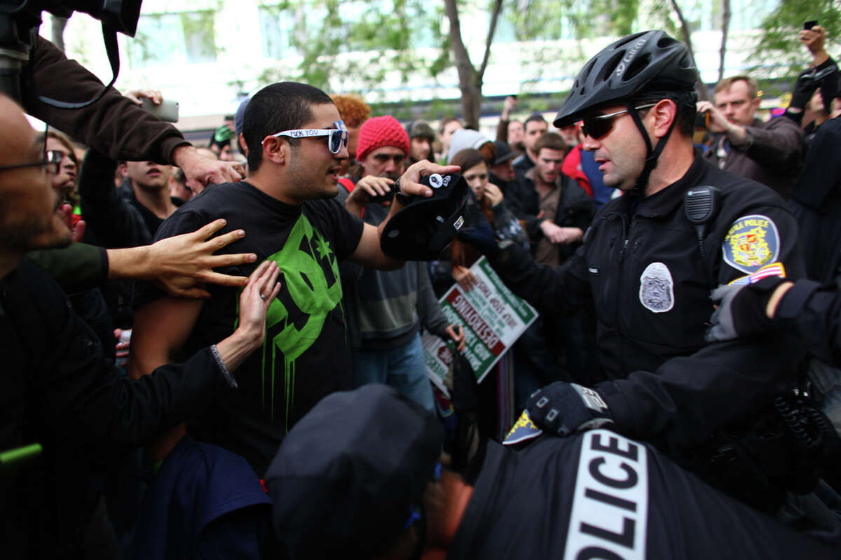 Protesters argue with Seattle police officers during the