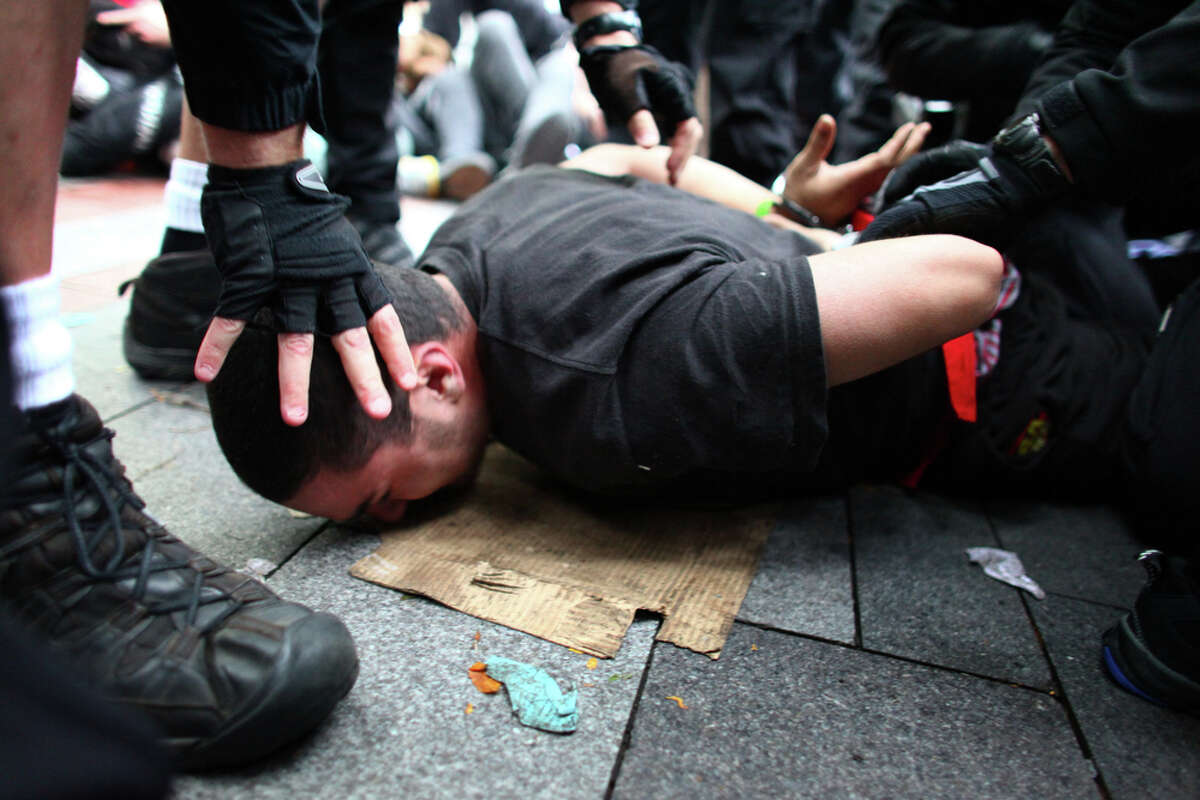 A protester attempting to block the removal of a tent in forced to the ground during the Occupy Seattle protest at Westlake Park on Wednesday, October 5, 2011 in Seattle. The protest mirrored the Occupy Wall Street protest in New York. Protesters were ordered to remove their encampment from the park, leading to arrests of people that refused to move.