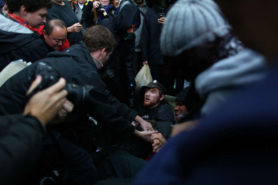 People fall to the ground during a scuffle between protesters and police. Photo: JOSHUA TRUJILLO / SEATTLEPI.COM