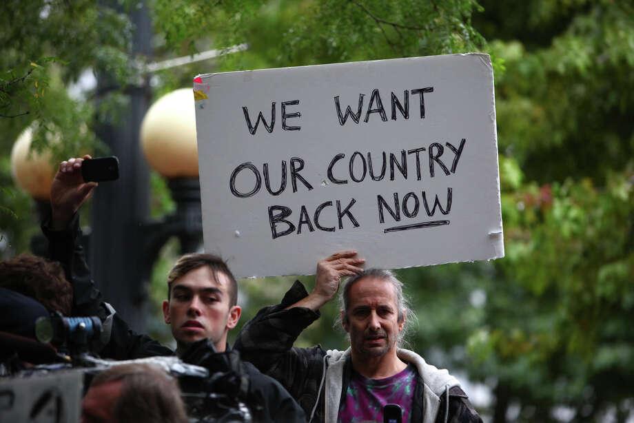 A protester holds a sign. Photo: JOSHUA TRUJILLO / SEATTLEPI.COM