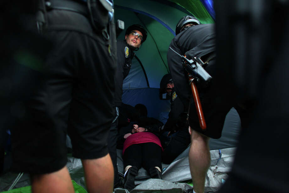 Seattle police officers work to remove people from tents. Photo: JOSHUA TRUJILLO / SEATTLEPI.COM