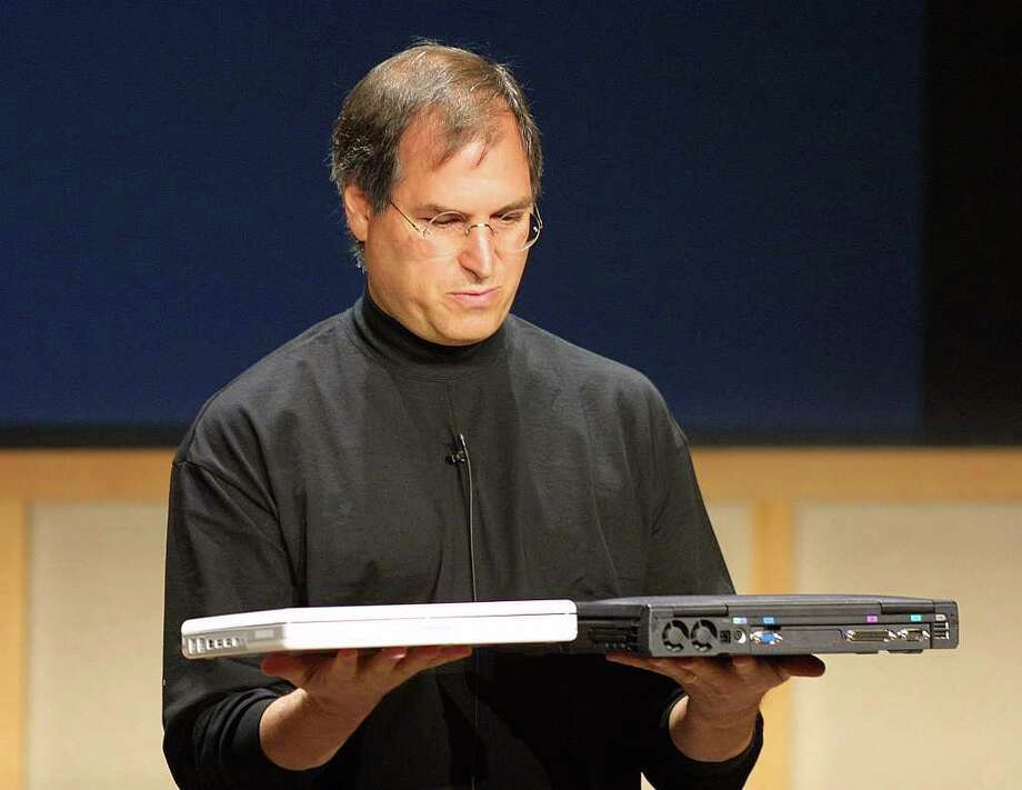 "iBook G3 notebook (2001):  The new all-white iBook reduced the bulk of the ""clamshell"" version and was lighter and faster than ever before. Here, Steve Jobs compares the weight of the all new iBook to arch-rival Dell's competing notebook. Photo: JOHN G. MABANGLO, AFP/Getty Images / AFP"