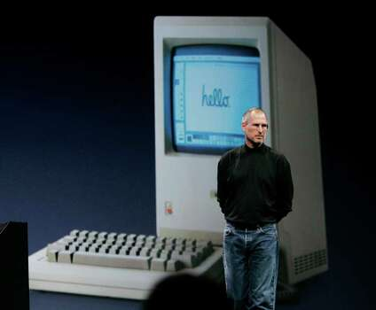 "Apple CEO Steve Jobs stands in front of an image of an early Apple desktop computer during his keynote address at MacWorld Conference & Expo in San Francisco, Tuesday, Jan. 9, 2007. Jobs is expected to use his speech at the Apple Worldwide Developers Conference on Monday to highlight the upcoming release of Mac OS X, showing that Apple remains a computer company even after dropping ""Computer"" from its name in January.  The slickness of its designs notwithstanding, the key to Apple's success and reputation for ease of use is its software and how well it integrates with its hardware.  (AP Photo/Paul Sakuma) Photo: Paul Sakuma, ASSOCIATED PRESS / AP2007"