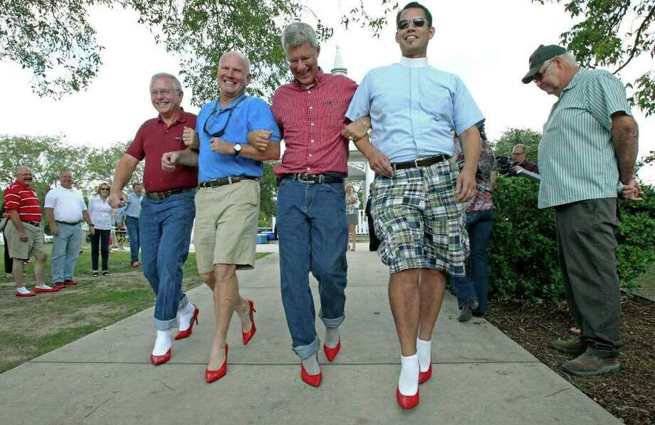"Bruce Calder, Randy Dent, Ben Adam and Bill Allport walk by spectator Butch Wood who was observing the Best in Heels contest during the ""Walk a Mile in Her Shoes"", a fundraiser and awareness-raiser for Domestic Violence Awareness Month. Photo: TOM REEL, SAN ANTONIO EXPRESS-NEWS / © 2011 San Antonio Express-News"