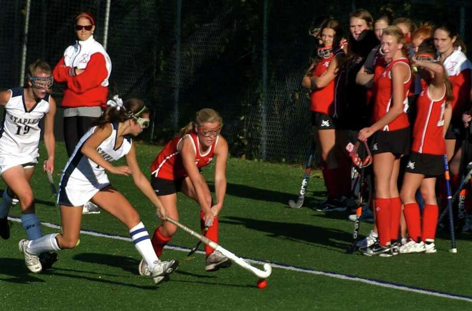 Staples' #1 Caroline Kearney, left, and New Canaan's #7 Abbey Buckenheimer chase down the ball, during girls field hockey action in Westport, Conn. on Wednesday October 5, 2011. Photo: Christian Abraham / Connecticut Post