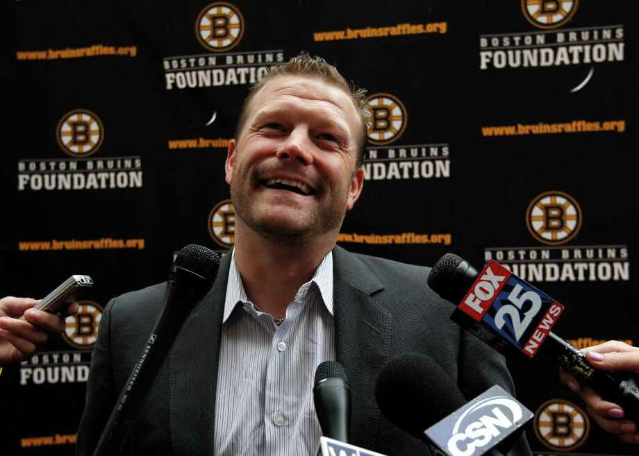 Boston Bruins NHL hockey goalie Tim Thomas speaks with members of the media as he arrives at the Boston Harbor Hotel, in Boston, Tuesday, Oct. 4, 2011, before the unveiling of the Stanley Cup rings at a ceremony for the Stanley Cup winning hockey team. (AP Photo/Steven Senne) Photo: Steven Senne / AP