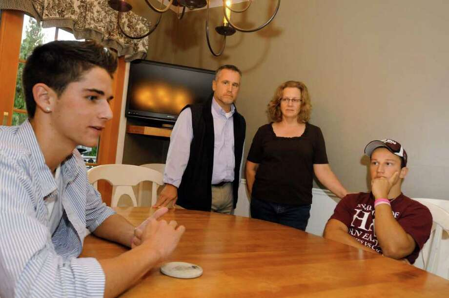 Brother Cody,left, and parents Mike and Natalie Mooney with their son Brandon, a senior Burnt Hills High School football player, talk about the concussion Brandon suffered during a recent game in Charlton, NY Tuesday Oct. 4, 2011.( Michael P. Farrell/Times Union) Photo: Michael P. Farrell