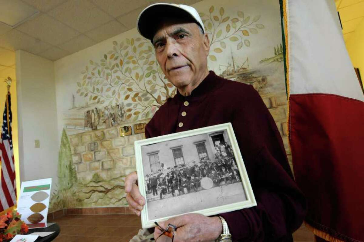 Philip J. DiNovo, executive director of The American Italian Heritage Association, holds a photograph of a Columbus Day parade band circa 1940's in Colonie, NY Wednesday Oct. 5, 2011.( Michael P. Farrell/Times Union)