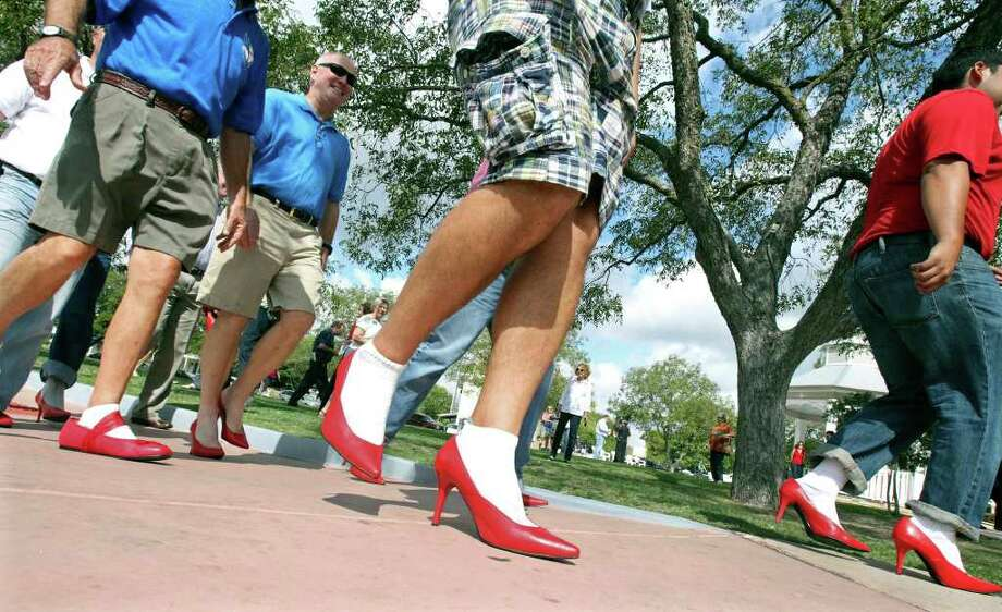 "Men wearing high heels circle Main Plaza during ""Walk a Mile in Her Shoes,"" a fundraiser for the Kendall County Women's Shelter and an awareness raiser for Domestic Violence Awareness Month, on Wednesday, Oct. 5, 2011. Photo: Tom Reel/treel@express-news.net / © 2011 San Antonio Express-News"