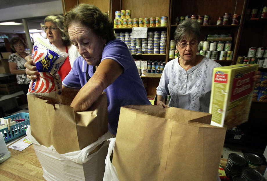 Volunteers Patty Everett (right) and LaVerne Parker fill food bags for families at Christian Assistance Ministry on Tuesday, Oct. 4, 2011. Photo: Bob Owen/rowen@express-news.net / rowen@express-news.net