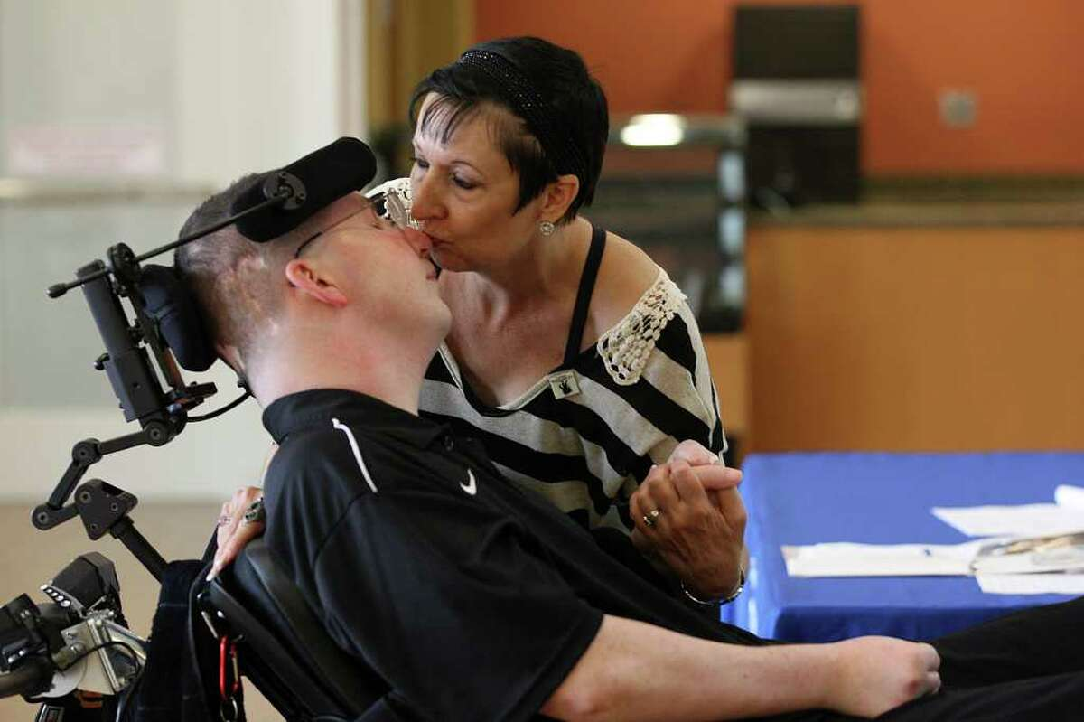 Cynde Harmon kisses her son Chris Harmon, who was injured by a drunken driver in Indiana, at the Polytrauma Rehabilitation Center.