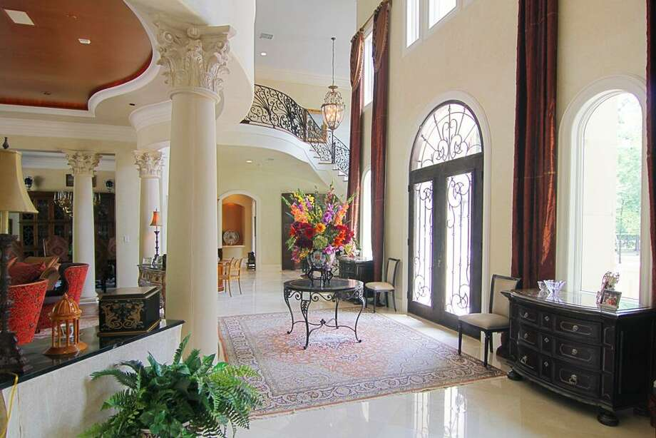 The two-story foyer features Corinthian columns and marble  flooring. Photo: RealEstate.MarthaTurner.com