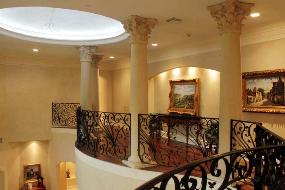 The second-floor hallway features hardwood flooring and a wrought-iron railing. Photo: RealEstate.MarthaTurner.com