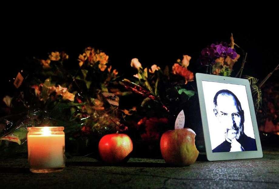 Una fotografía de Steve Jobs, cofundador y ex presidente ejecutivo de Apple Inc., es reflejada en un iPad con flores y manzanas afuera de la residencia de la familia de Jobs en Palo Alto, California. Jobs, quien revolucionó el mundo de la tecnología, falleció el miércoles a los 56 años de edad. Photo: Tony Avelar / © 2011 Bloomberg Finance LP