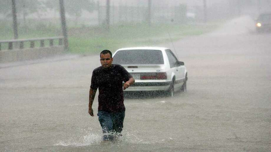 Mario Vasquez leaves his stalled car on South Flores and Sixmile Creek on August 16, 2007. The creek flooded with rains from Tropical Storm Erin. Photo: JERRY LARA, SAN ANTONIO EXPRESS-NEWS / SAN ANTONIO EXPRESS-NEWS