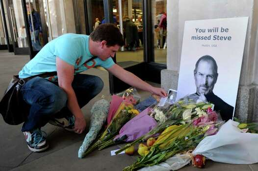 A man reads a note left with flowers and a picture of Steve Jobs outside the Apple store in Covent Garden, central London, on October 6, 2011, following the death of Steve Jobs, co-founder and former chief executive of US technology giant Apple, at the age of 56. Millions of people paid emotional tribute today to the late Steve Jobs, praising the Apple founder's vision and creative genius which has left behind a world transformed by his legacy. AFP PHOTO / CARL COURT Photo: CARL COURT, Getty / AFP