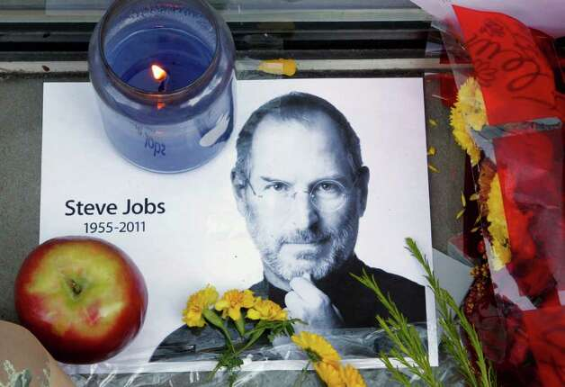 A photograph of Apple co-founder Steve Jobs sits near a candle, an apple and flowers to form a portion of a tribute in front of an Apple store in Boston, Thursday, Oct. 6, 2011. Jobs died Wednesday at 56. (AP Photo/Steven Senne) Photo: Steven Senne, Associated Press / AP