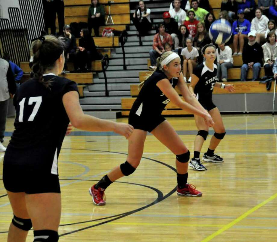 Staples' Joosje Grevers, middle, returns it Monday against Darien. Grevers had 17 kills and eight service aces Wednesday in a 3-1 victory over Wilton. Photo: Suzanne Kalb / Contributed Photo