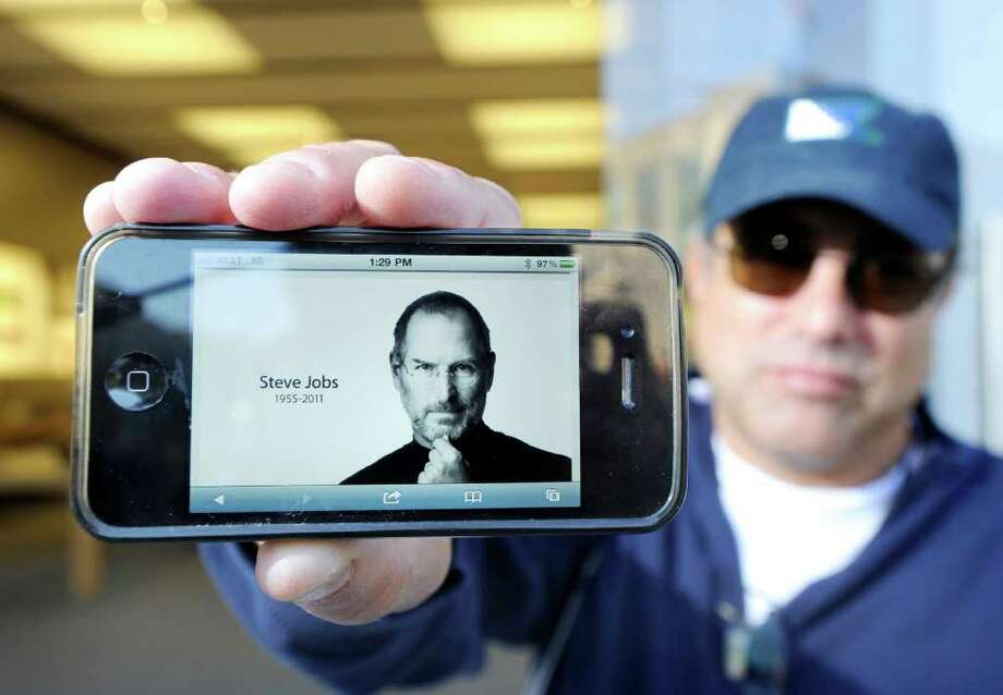Jeffrey Kay of Greenwich displays an image of Steve Jobs from the Apple website on his iPhone while standing in front of the Apple store at 356 Greenwich Ave.Thursday afternoon, Oct. 6, 2011. Jobs, the co-founder and former CEO of Apple, died Wednesday at the age of 56. Photo: Bob Luckey / Greenwich Time