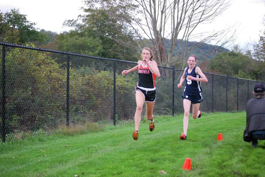 Staples' Caroline Koenig, right, tries to catch up with a Ridgefield runner Tuesday. Koenig placed third overall as host Ridgefield took the top two spots and swept the meet. The Lady Wreckers defeated Bassick but lost to Fairfield Warde to go 1-2 overall. Photo: Megan Smith / Contributed Photo