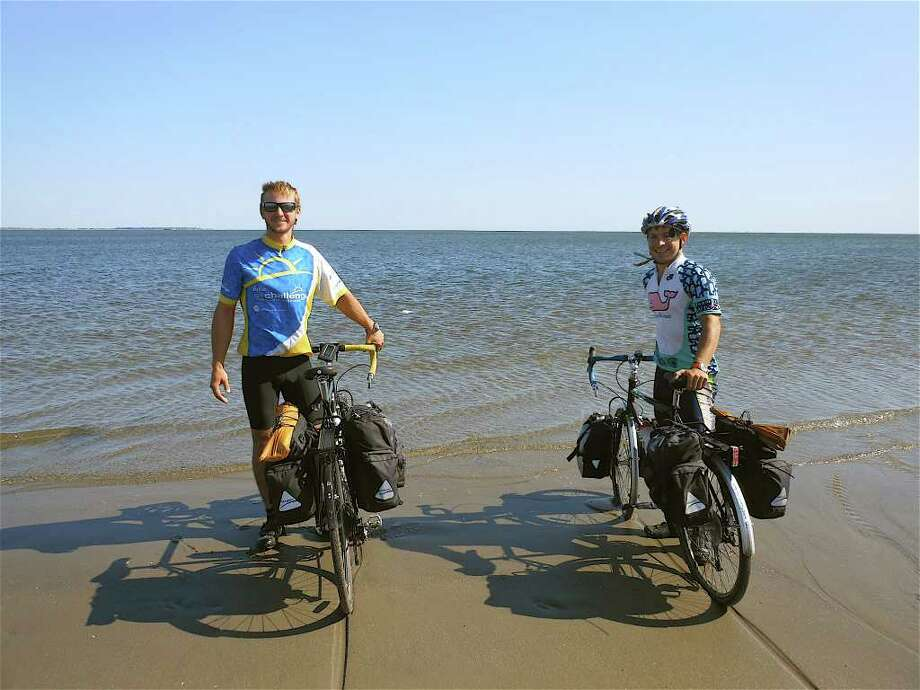 Joe Ruscito and Lucas Gubinski celebrate their cross-continental bicycle ride for charity conclusion Wednesday at their hometown's Penfield Beach. Photo: Mike Lauterborn / Fairfield Citizen contributed
