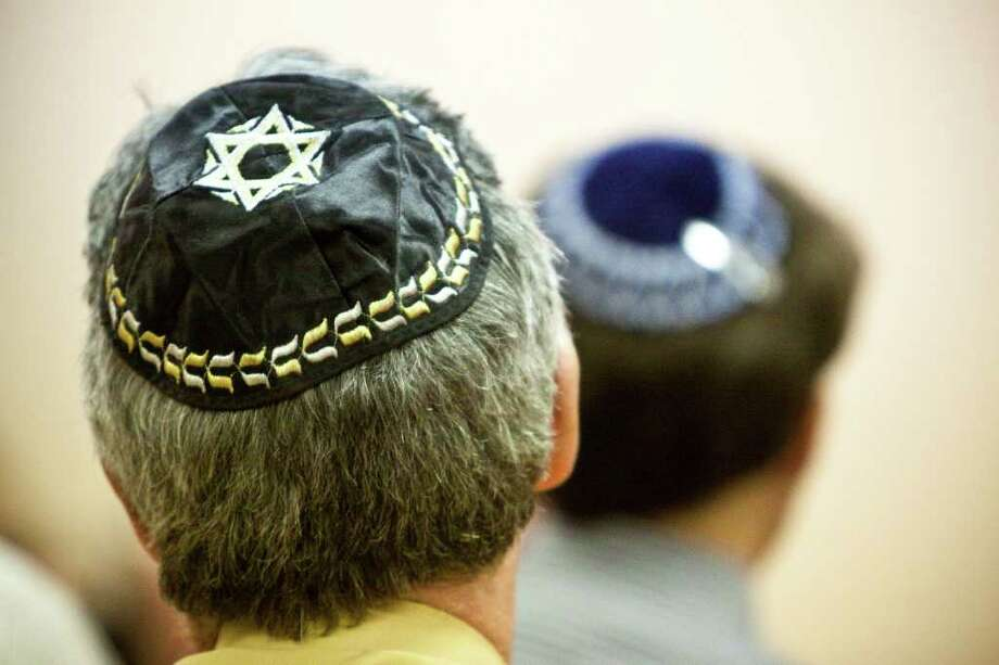Participants wait for the beginning of services during Erev Rosh Hashanah, Sept. 28, 2011 in Houston at Hillel Student Center. Rosh Hashanah is the Jewish New Year. The head covering is a called a kippah, a traditional head covering Jews wear, especially during prayer. (Eric Kayne/For the Chronicle) Photo: Eric Kayne / © 2011 Eric Kayne