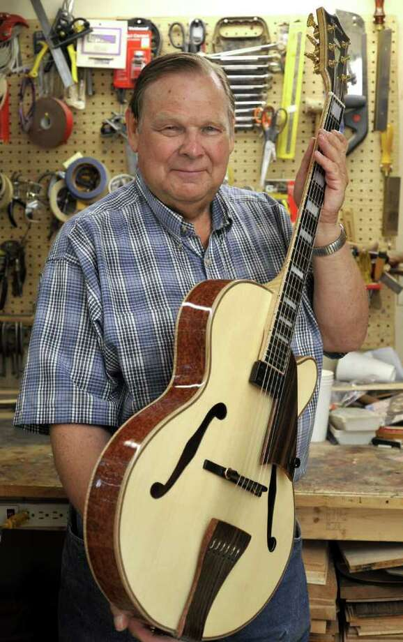 Carl Barney, 71, holds a finished archtop guitar with bubinga back and sides. Bubinga is an Africian wood. Barney makes classical guitars but his specialty is jazz guitars. He is seen here in his Southbury workshop Monday, Sept. 26, 2011. Photo: Michael Duffy / The News-Times