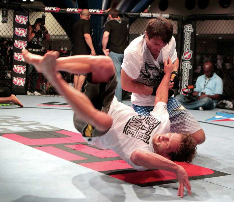 Chael Sonnen flips Gary Maynard at the center of the octagon during workouts for UFC 136 at George R. Brown Center. Both fighters will be competing Saturday, October 8, 2011 at Toyota Center  in UFC 136. Photo: Billy Smith II, Chronicle / 2011 Chronicle