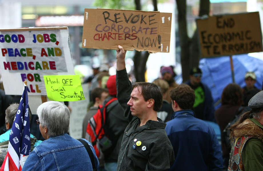 Protesters hold signs during the Occupy Seattle protest at Westlake Park on Wednesday, October 5, 2011 in Seattle. The protest mirrored the Occupy Wall Street protest in New York. Photo: JOSHUA TRUJILLO / SEATTLEPI.COM