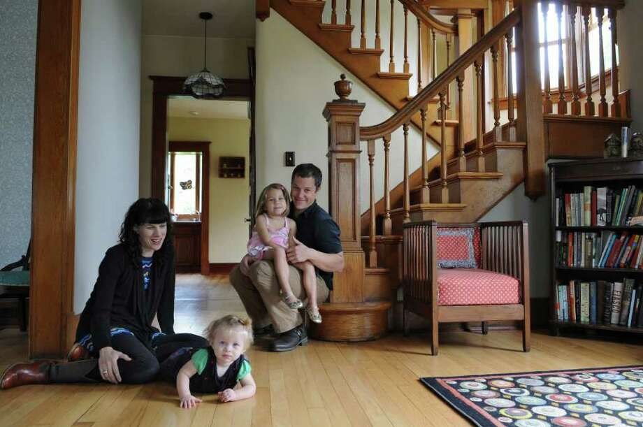 Scott Waldman holds his daughter Madeline, while his wife Frances plays with daughter Phoebe in their home on Sunday Oct. 2, 2011 in Schodack Landing, NY. ( Philip Kamrass / Times Union) Photo: Philip Kamrass / 00014822A