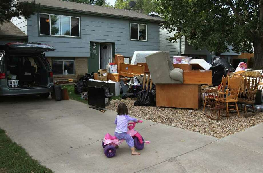 JOHN MOORE : GETTY IMAGES FORECLOSED:  Caitlin Barbiere, 2, plays as her family's goods are piled up in an eviction in Miliken, Colo. A glut of such foreclosures is expected to depress housing values for years. Photo: John Moore / 2011 Getty Images