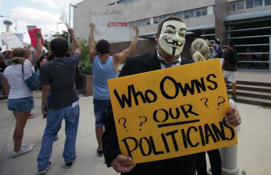 A protester holds a sign questioning the integrity of politicians in front of the Federal Reserve office in San Antonio on Thursday, Oct. 6, 2011. In support of the protesters at New York's Wall Street demonstration, about 100 people in San Antonio gathered to voice their opposition to the current financial state of affairs. The demonstrators gathered at Travis Park and marched toward the Federal Reserve office and around Main Plaza. No arrests or confrontations were witnessed at the mostly peaceful yet loud protest. Kin Man Hui/kmhui@express-news.net Photo: KIN MAN HUI, SAN ANTONIO EXPRESS-NEWS / SAN ANTONIO EXPRESS-NEWS