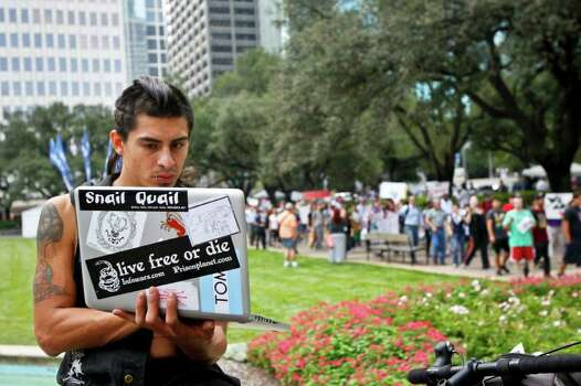 Derick Broze uses his computer's web cam to record video as he and other protestors with the Occupy Houston movement, an outgrowth of the Occupy Wall Street protests in New York, gather at City Hall in downtown Houston to denounce what they describe as social and economic equality and corporate greed, Thursday, Oct. 6, 2011, in Houston. Photo: Michael Paulsen, Houston Chronicle / © 2011 Houston Chronicle
