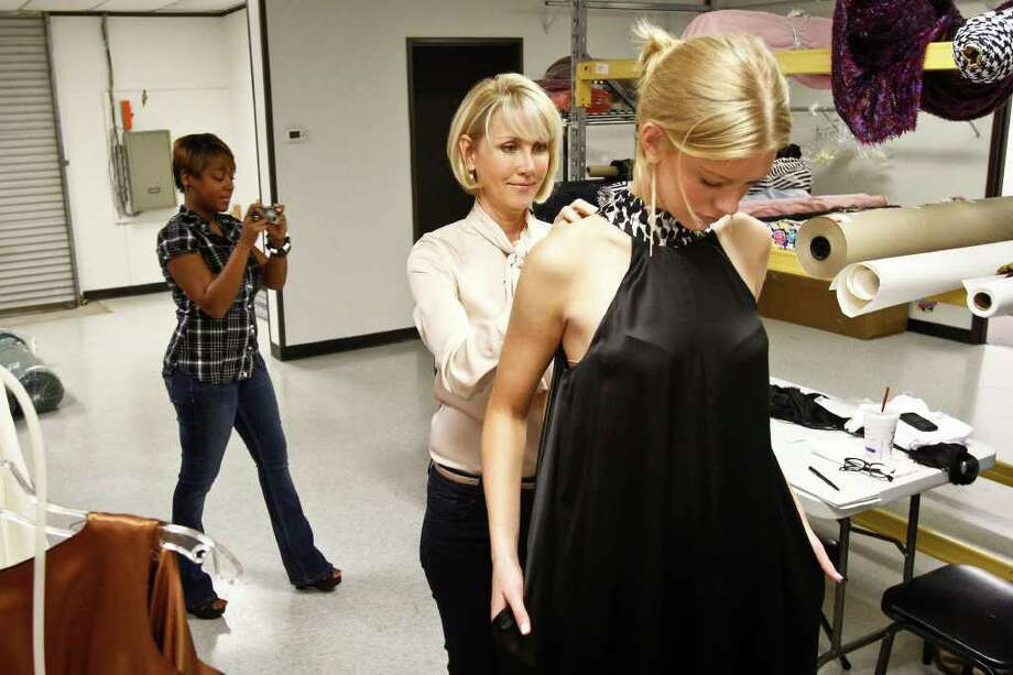 Houston fashion designer Jerri Moore (center) ties a bow around model Alyssa Pasek as design assistant Tanesha Seafous (left) takes a photo during a final fitting of Moore's collection for Fashion Houston, Tuesday, Sept. 27, 2011, in Houston.   ( Michael Paulsen / Houston Chronicle ) Photo: Michael Paulsen / © 2011 Houston Chronicle
