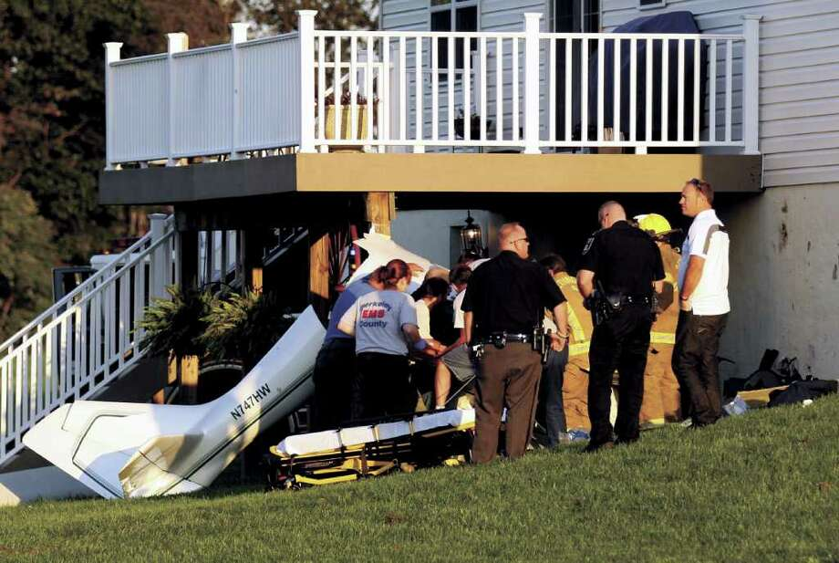 Emergency responders work to remove the pilot of a small, single-engine plane that crashed into a home  in Hedgesville, W. Va. early Wednesday evening. The pilot, Harry L. Weber, of Danbury, was killed in the crash. no one in the home was hurt. (Journal photo by Chris Jackson) Photo: Contributed Photo
