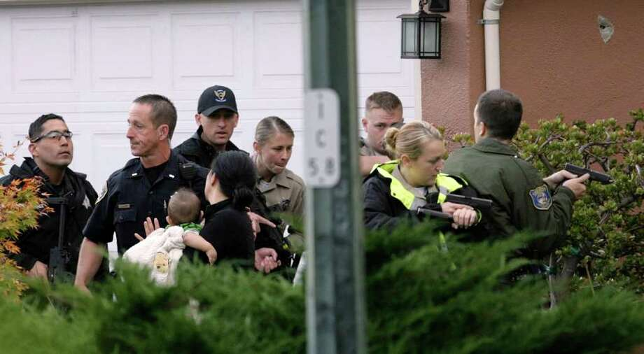 Sheriff's deputies escort a woman and baby out of a house before they enter the home in Sunnyvale, Calif., where a man matching the description of suspected gunman Shareef Allman was found and shot dead by law enforcement officers on Thursday, Oct. 6, 2011. Shareef was the focus of a huge manhunt after an alleged shooting at a Cupertino cement plant early Wednesday morning where three people were killed and seven wounded. (AP Photo/San Jose Mercury News, Gary Reyes) Photo: Gary Reyes