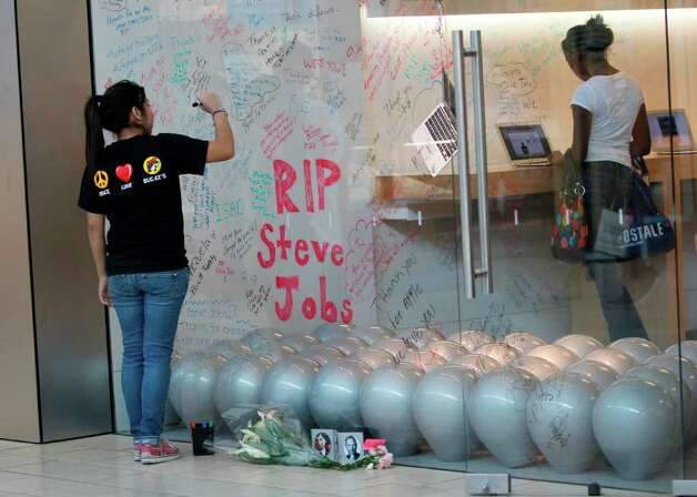 Mayra BeltrÀn  : Chronicle TRIBUTE IN HOUSTON: Jaqueline Hernandez, 17, writes a message Thursday outside an Apple Store in Memorial City Mall in honor of Steve Jobs,  co-founder and former chief executive officer of Apple. The high-tech pioneer died Wednesday at age 56. Photo: Mayra Beltran / © 2011 Houston Chronicle