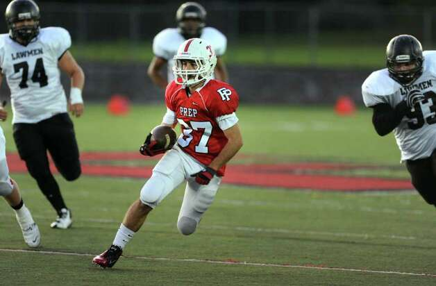 Fairfield Prep's Joseph McBride carries the ball past Jonathan Law defenders on his way to a 33 yard touchdown during their game Thursday Oct. 6, 2011 at Alumni Field at Fairfield University. Photo: Autumn Driscoll