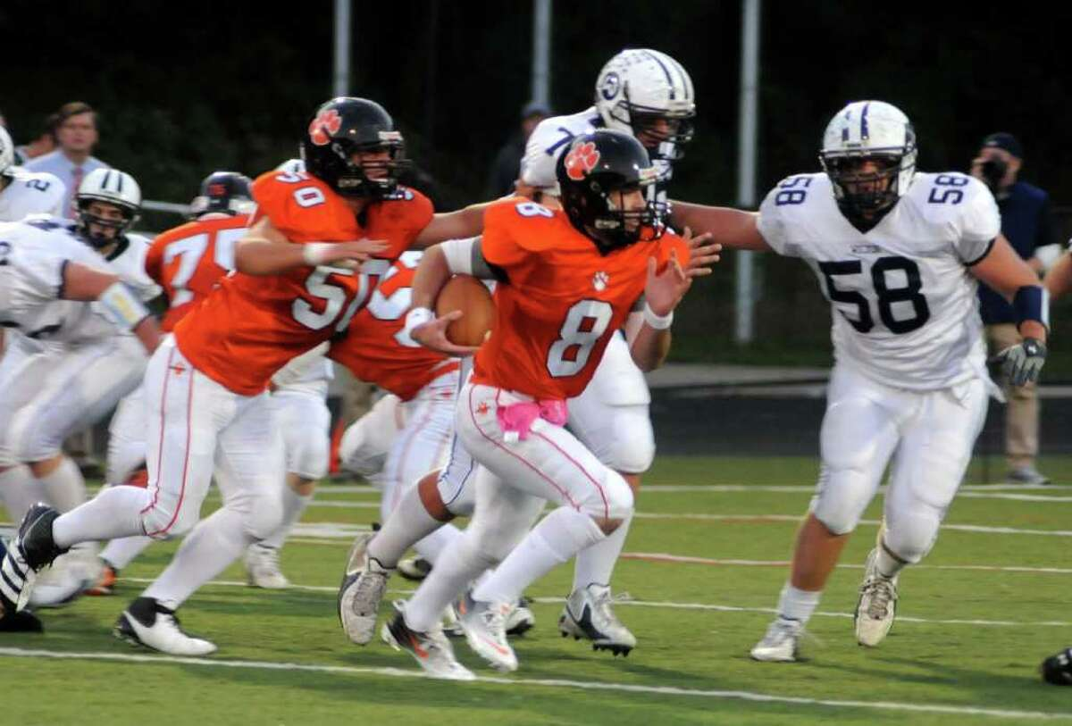 Ridgefield's QB #8, Connor Rowe, carries the ball against Wilton during Thursday nights game at Wilton High school on Oct. 6, 2011.